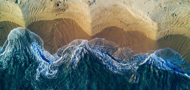 An aerial image showing ocean waves crashing onto a beach