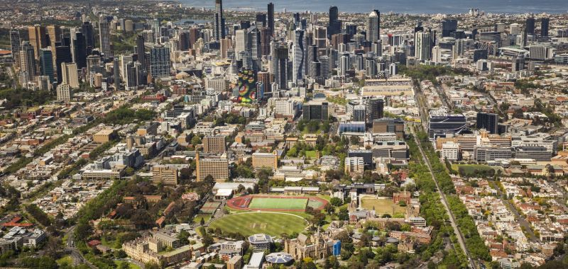 An aerial photograph of the University of Melbourne's Parkville campus, with Melbourne's CBD and Port Phillip Bay in the background