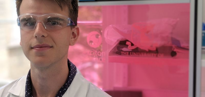 Exciton Science researcher Ben Tadgell wears a lab coat and protective glasses