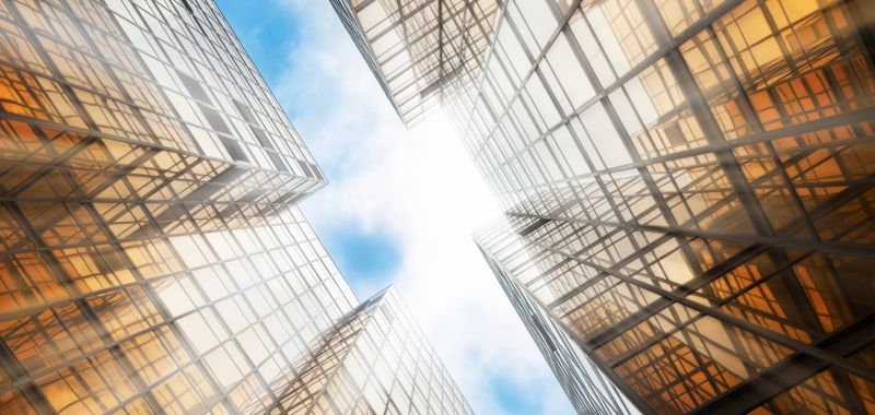 An image of sunlight and blue sky between two glass buildings