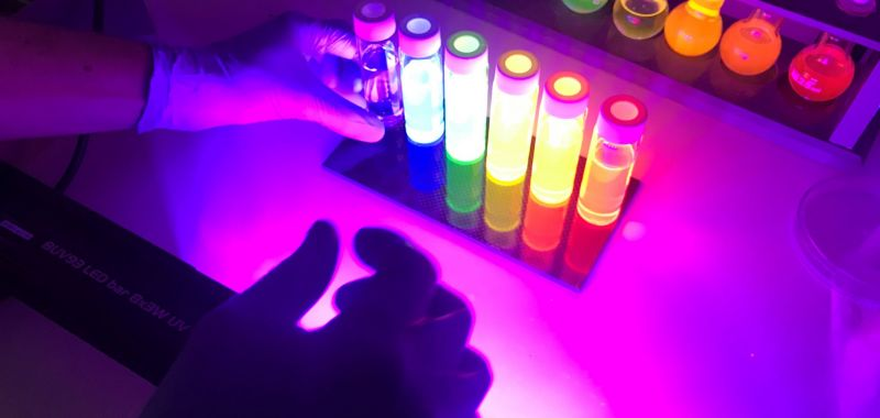 Vials of quantum dot solutions fluorescing in the Exciton Science lab