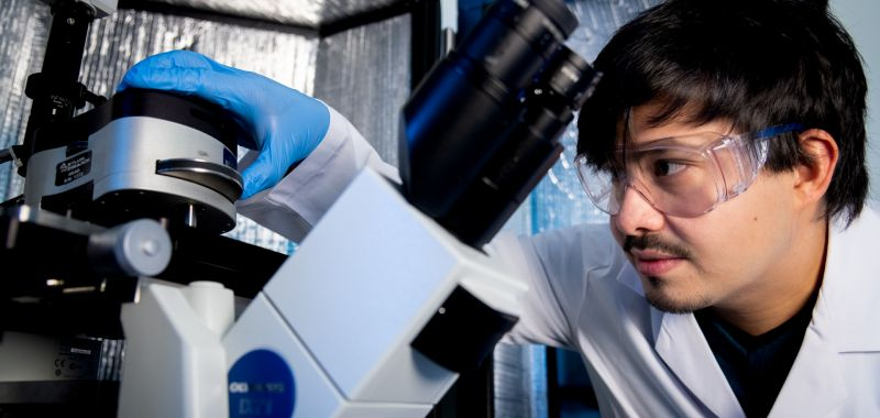 Dr Eser Akinoglu working with a microscope at The University of Melbourne