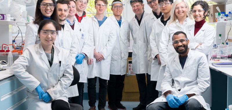 Members of the Nanoscience Lab at the University of Melbourne's School of Chemistry pose for a picture wearing white lab coats and clear plastic safety goggles