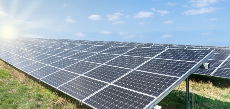 An image of solar panels in a field under sunlight