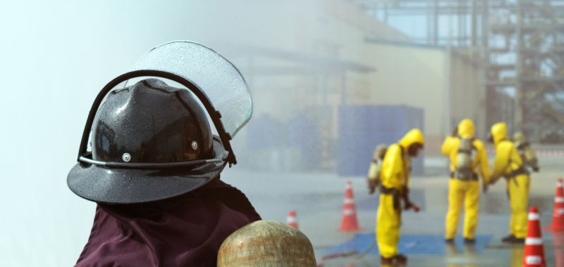 An image of a firefighter wearing equipment watching emergency services wearing chemical hazard protection equipment
