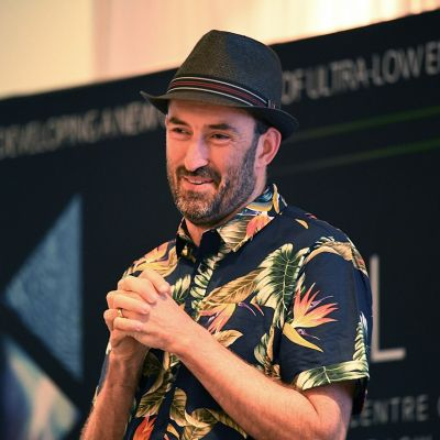 Exciton Science Chief Investigator Jared Cole addressing an audience while wearing a short sleeved shirt and a trilby hat