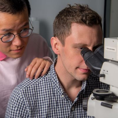 Lead author Heyou Zhang (left) and collaborator Calum Kinnear (right) working with a microscope