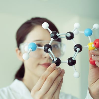 A scientist in a white coat holds up a model of a chemical structure