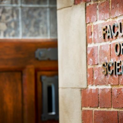 An image of the Faculty of Science at the University of Melbourne, showing a red brick wall and a wooden door