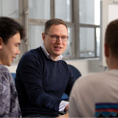 Exciton Science's Ivan Kassal is pictured in a meeting room at the University of Sydney wearing a blue jumper with two younger reseachers either side of them in the foreground