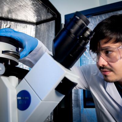 Dr Eser Akinoglu working with a microscope and wearing safety goggles and a white lab coat at The University of Melbourne