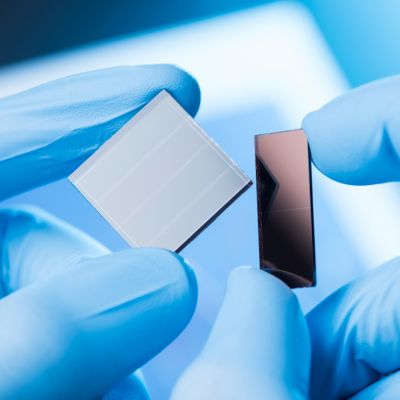 An image of a gloved hand holding prototype solar cells