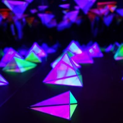 An image of triangular graphics in green and purple fluorescent colours