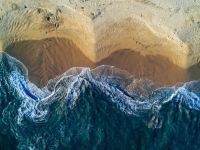 An aerial image showing ocean waves crashing onto a beach