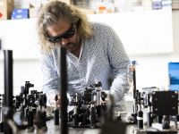 Professor Tim Schmidt wearing protective goggles working in a laser equipment laboratory at UNSW Sydney.