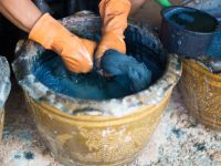 A person wearing orange gloves dyes fabric in a blue liquid