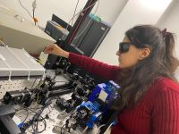 Dr Elham Gholizadeh, wearing a red jumper and black protective goggles, working with spectroscopy equipment in a laboratory at UNSW Sydney