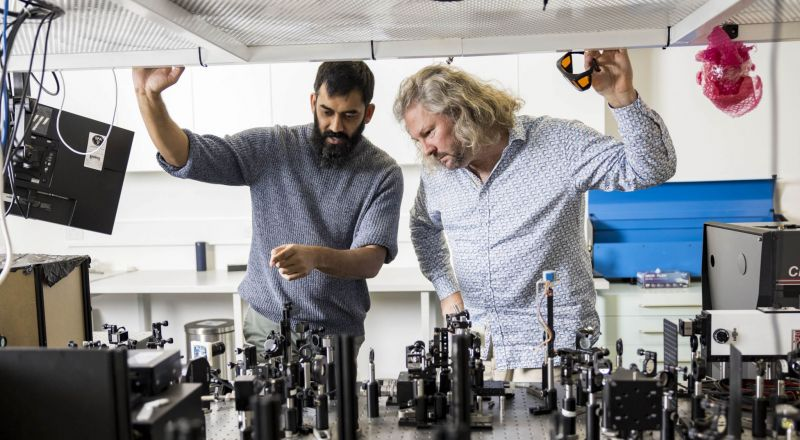 Shyamal Prasad (left) and Tim Schmidt (right) working in a laser lab at UNSW in Sydney