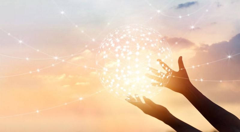 A creative image of hands holding up a representation of light and energy in the sky