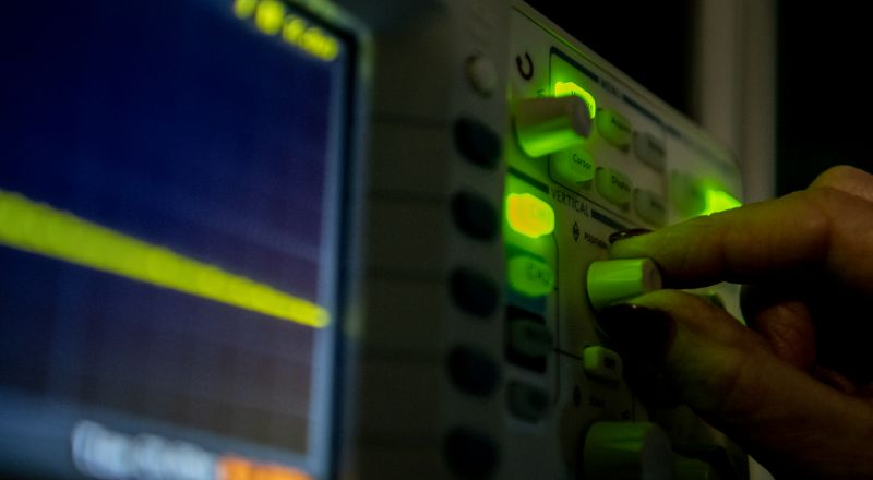 An image of a hand operating the dials of equipment located in the laser lab at University of Melbourne's School of Chemistry