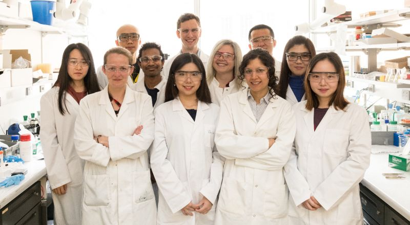 A group of men and women researchers wearing white lab goats and safety googles face the camera in a laboratory