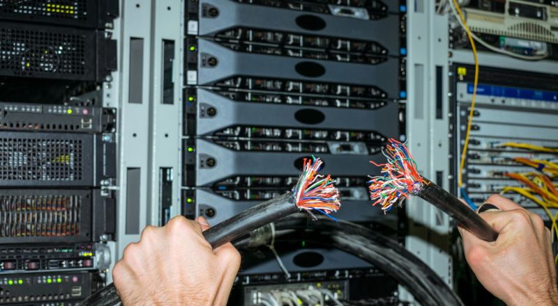 A pair of hands holding a severed cable in front of a computer server